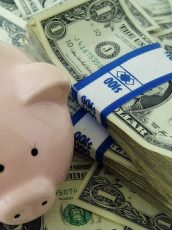 a pink piggy bank and a stack of dollar bills