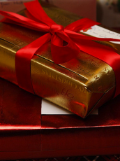 stack of gifts wrapped in gold and red wrapping paper with a red bow