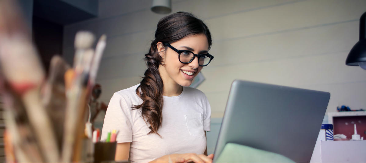 woman with glasses smiling and looking at a computer