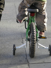 young child riding on a bike with an adult walking next to him