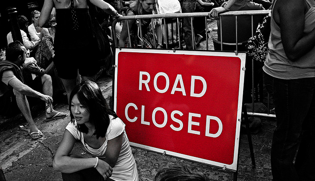 road closed sign with people sitting and standing around