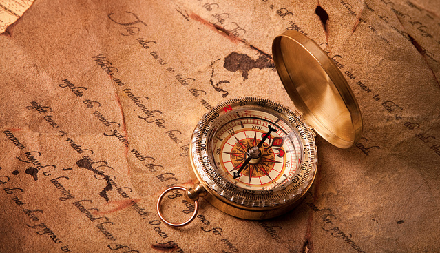 an old style compass sitting on a letter