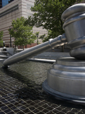 a large statue of a gavel in the middle of a park