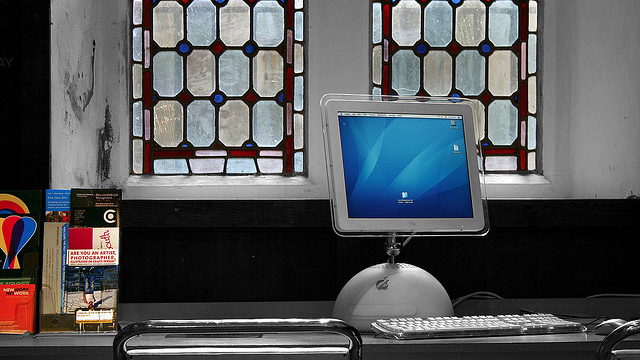 an old computer sitting in front of a mosaic window