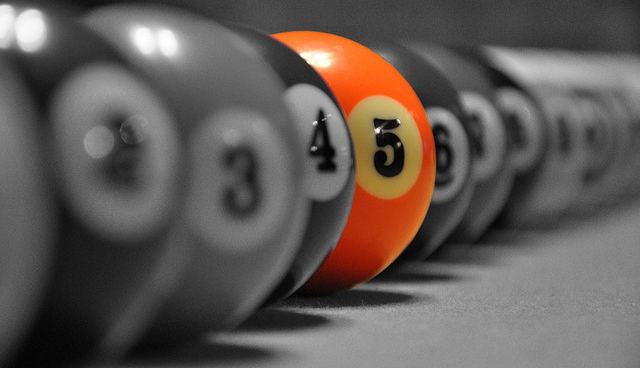 black and white line of pool balls and one orange pool ball with the number 5 on it