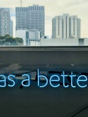 neon sign that says data has a better idea in front of a cityscape