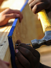 one person holding wood in place and the other hammering two pieces together