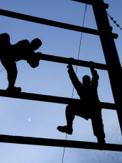 two men climbing up a scaffolding