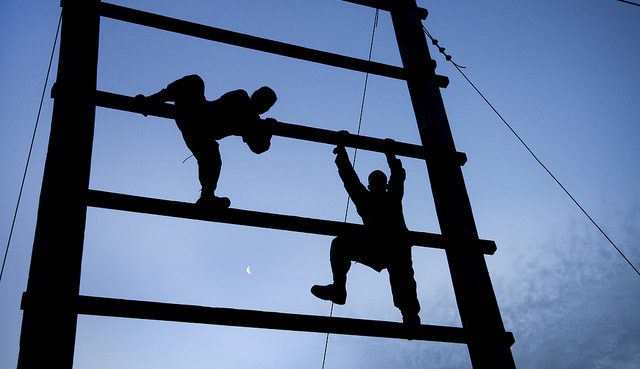 two men climbing up a scaffolding