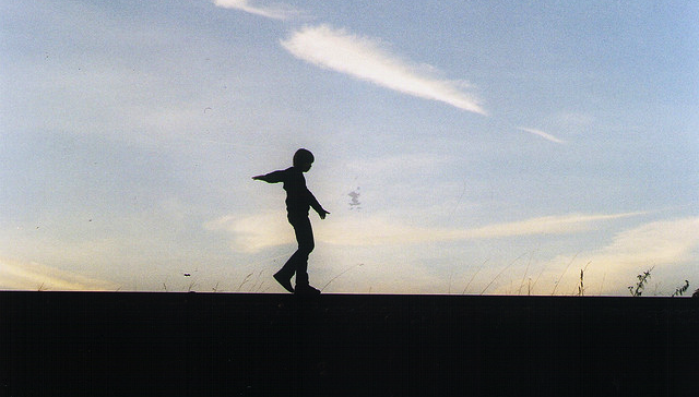 silhouette of a young boy against a pale blue sky