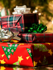 stack of present wrapped in holiday wrapping paper with gold bows under a tree