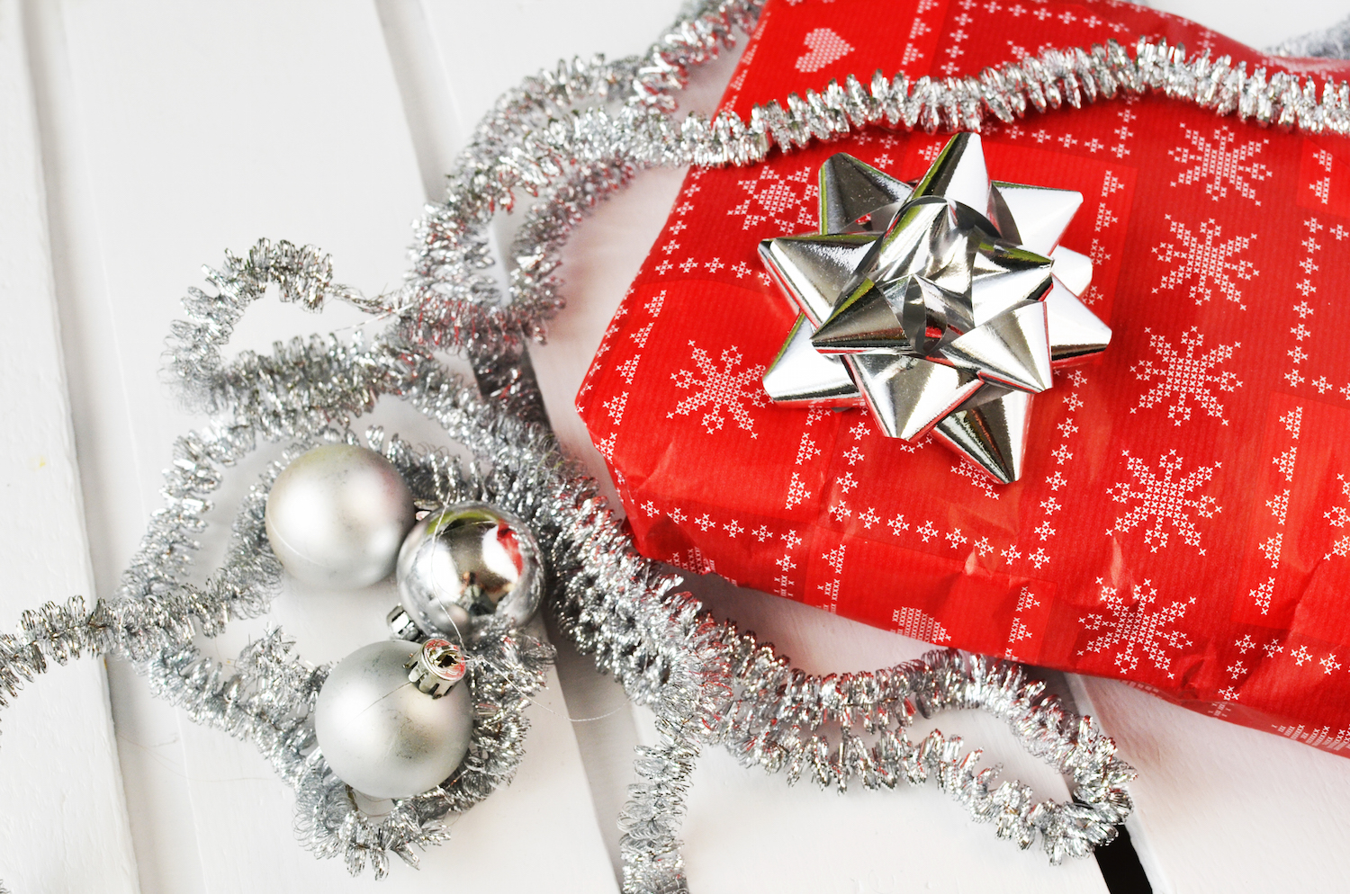 red gift wrapped present with a silver bow and tinsel holiday decorations