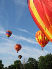 colorful hot air balloons taking off from a field