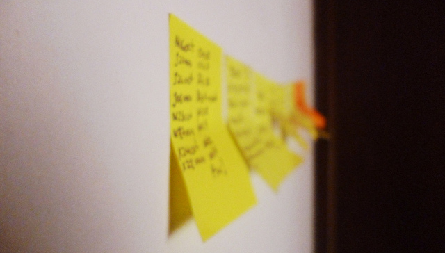 yellow sticky notes in a line on a wall