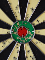 spinning target on a dartboard with darts