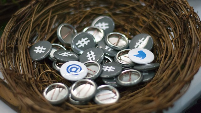 pins with social media icons on them in a wicker basket