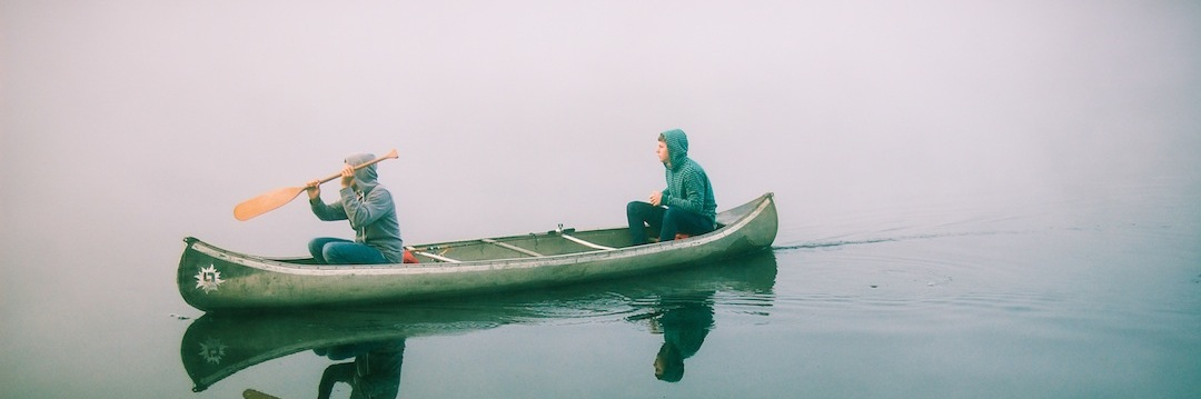 two guys sitting in a boat out on the water with one paddle