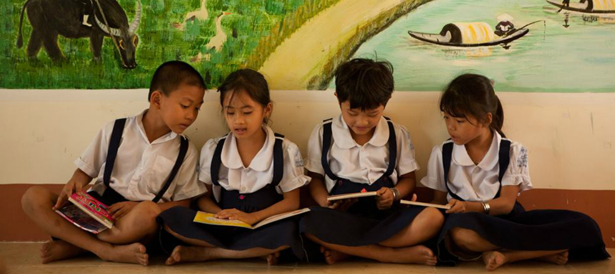young group of students in uniforms sitting against a wall and reading books