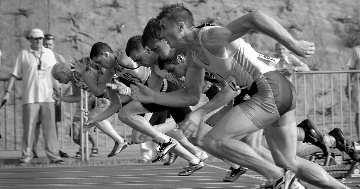 black and white men running a race