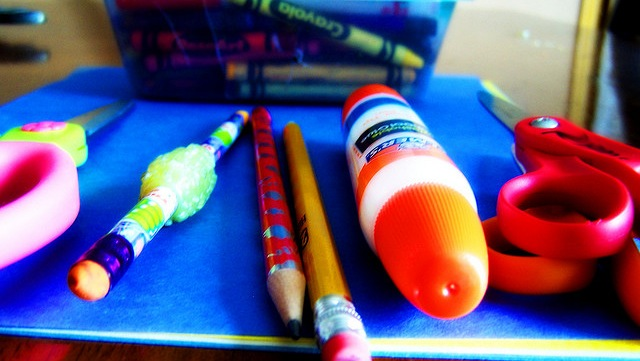 crayons glue sticks and pencils laying on a notebook