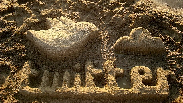sand sculpture drawings of people and a whale