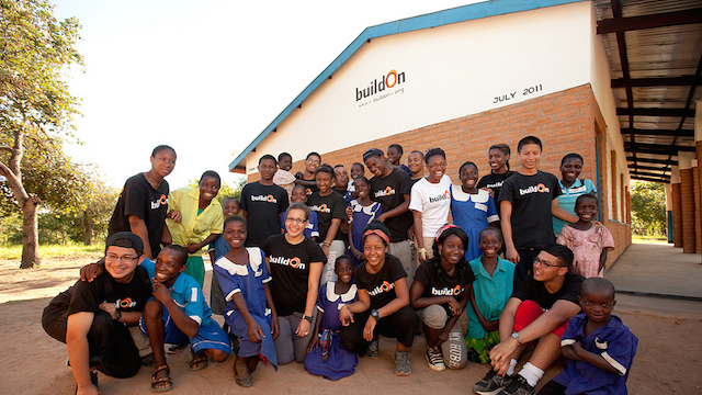 BuildOn volunteers and students posing in front of a BuildOn school in Malawi