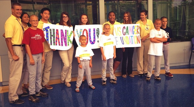 children and people with yellow shirts holding thank you vs. cancer signs