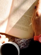 arms with a pink watch holding a book and holding a cup of coffee