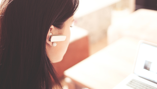 woman with brown hair with a bluetooth earpiece