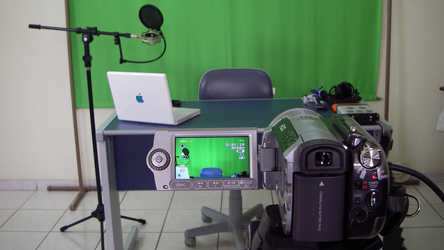 video camera recording a table in front of a green screen