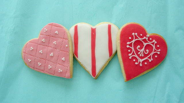 heart sugar cookies with pink white and red frosting on a blue background