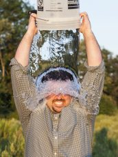 man in a grey button up dumping a water bucket onto his head in a field for a fundraising event
