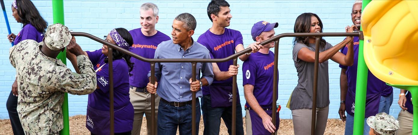 The Obamas working with volunteers in purple t-shirts to build a playground structure