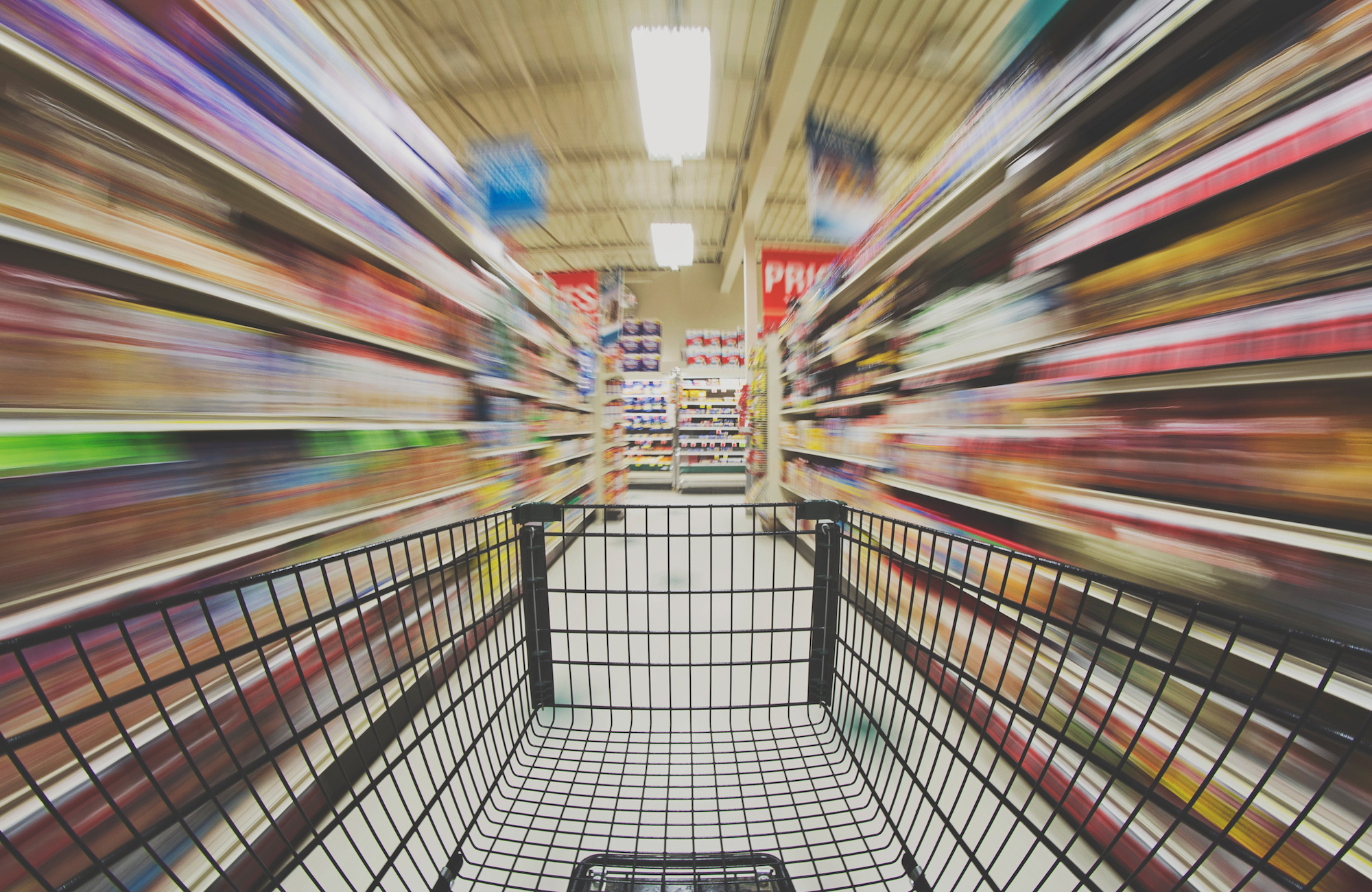 blurry grocery store aisles person pushing a cart