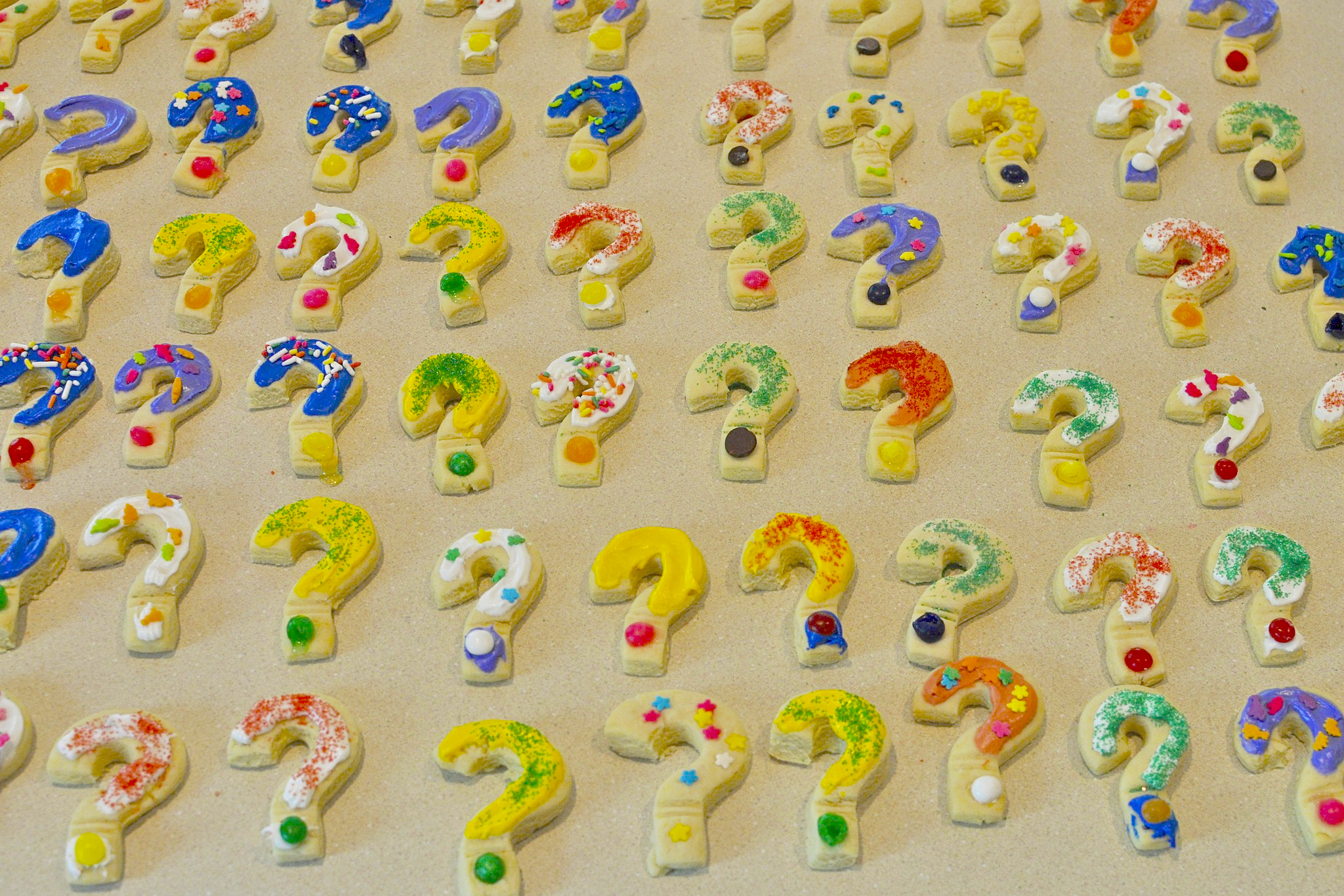 sugar cookies with colorful frosting in the shape of a question mark