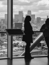 three women looking out over a cityscape looking at a view