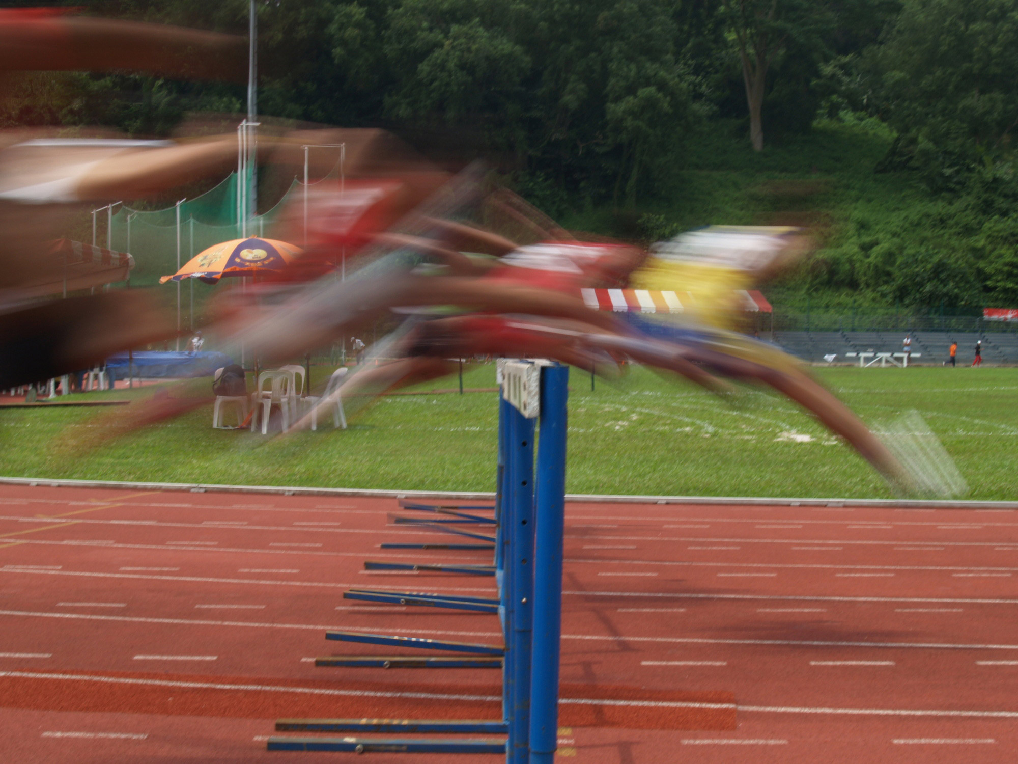 blurry photo of runners jumping over a hurdle