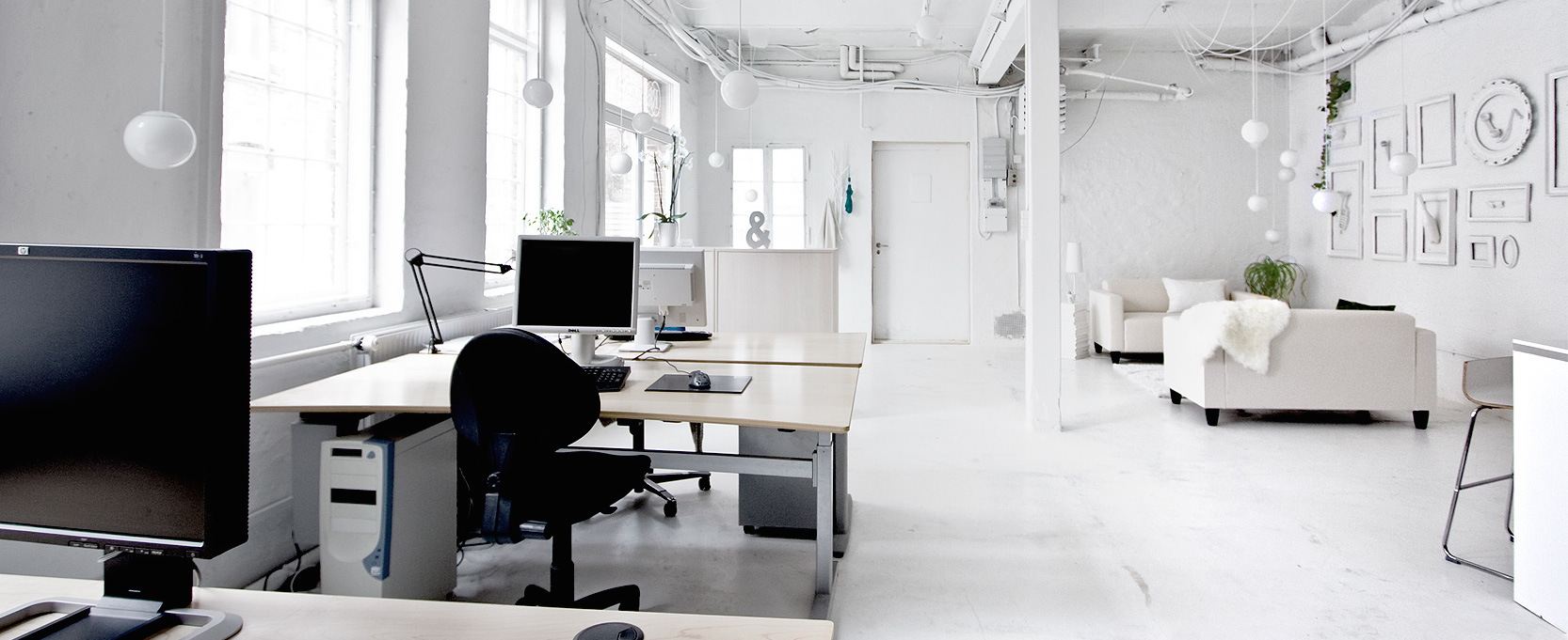 all white workplace with desks and couches