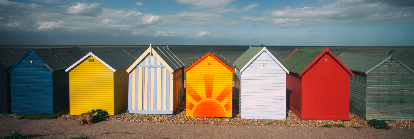 line of different colored painted sheds, one painted with an orange sun in a field