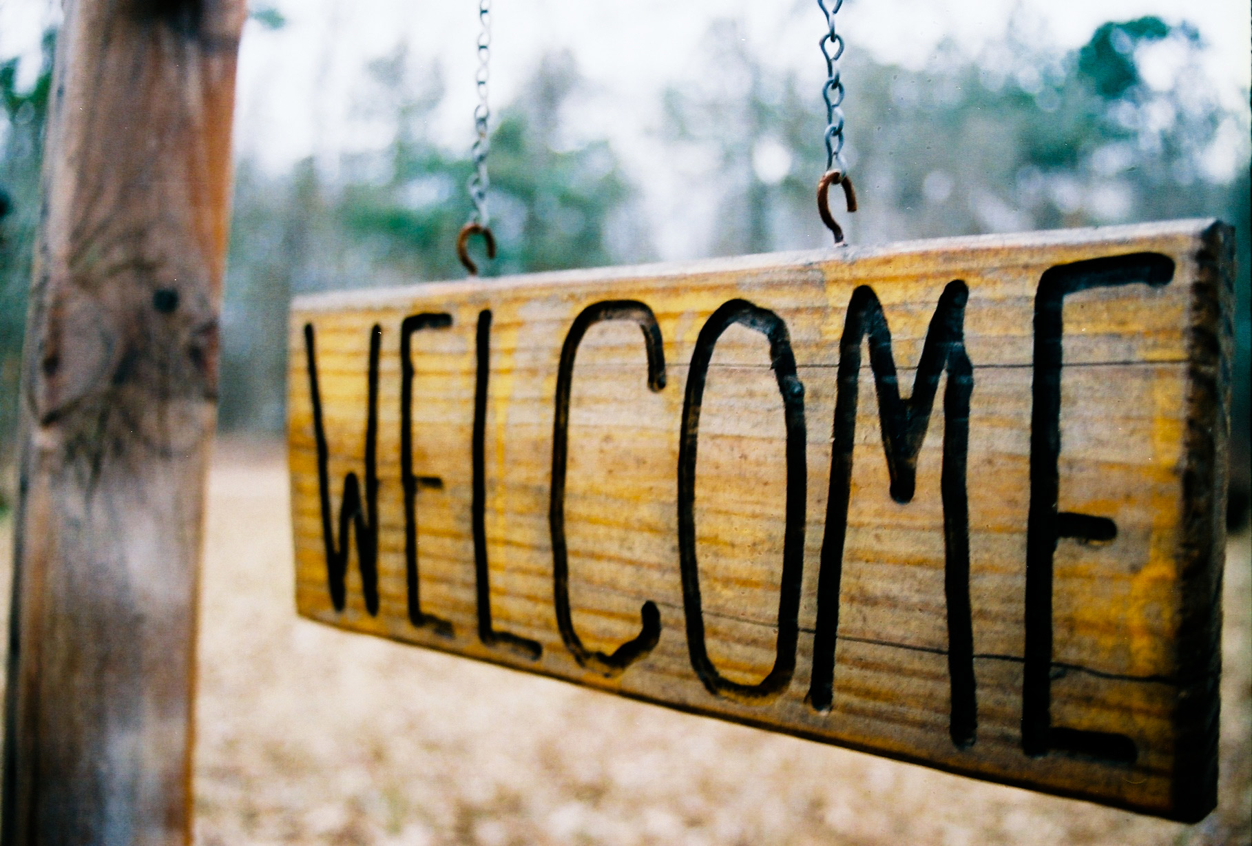 wood swinging welcome sign