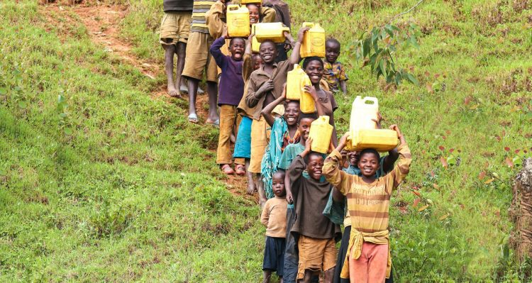 Image of individuals carrying water