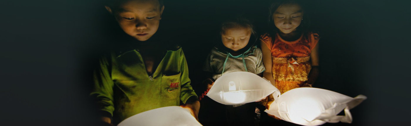 two young children looking down into a light