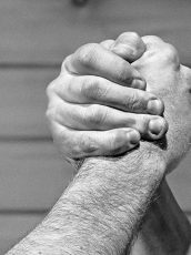 black and white photo of two men clasping hands
