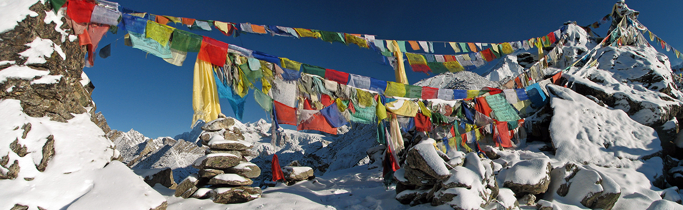 colorful clothes hanging on strings over snowy mountains