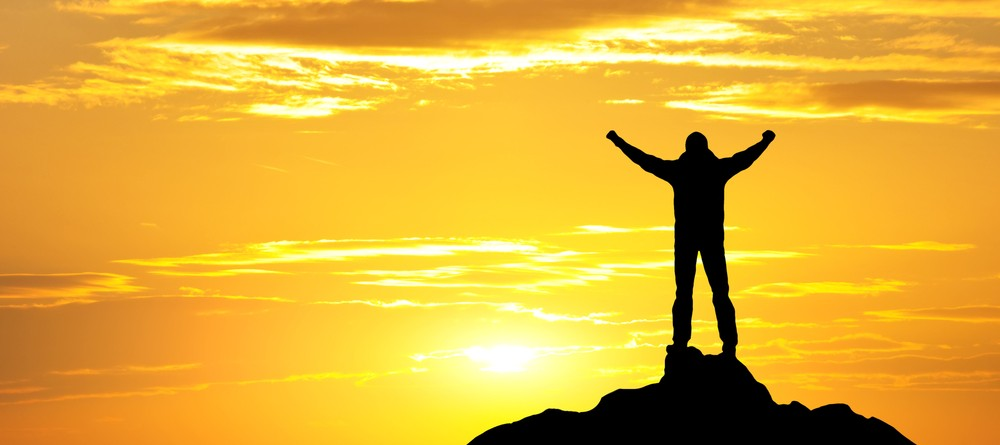 the sun beginning to rise and a man facing it arms raised standing on a rock