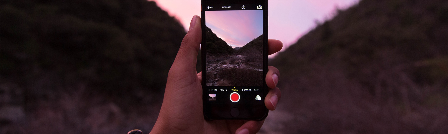person holding up a mobile phone and taking a photo of mountains and a sunset