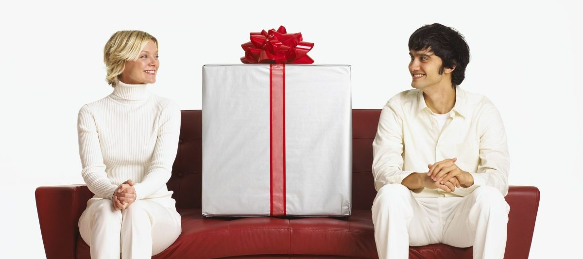 two people dressed in white sitting on a red couch with a white gift in between them