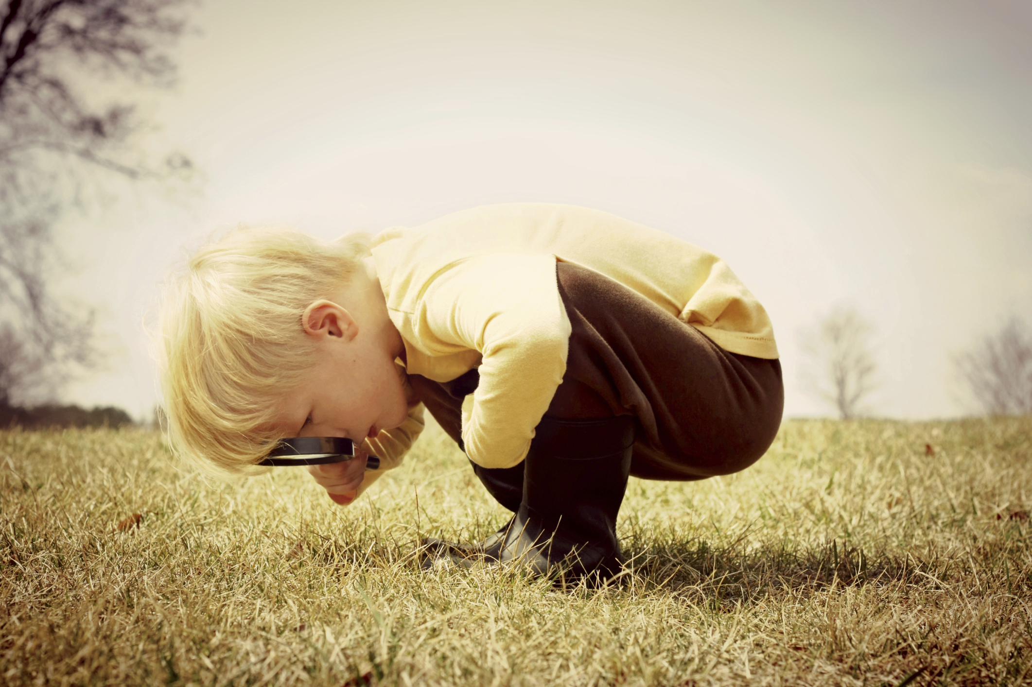 young boy bent over looking at the grass