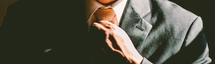 Close up of man straightening his tie.