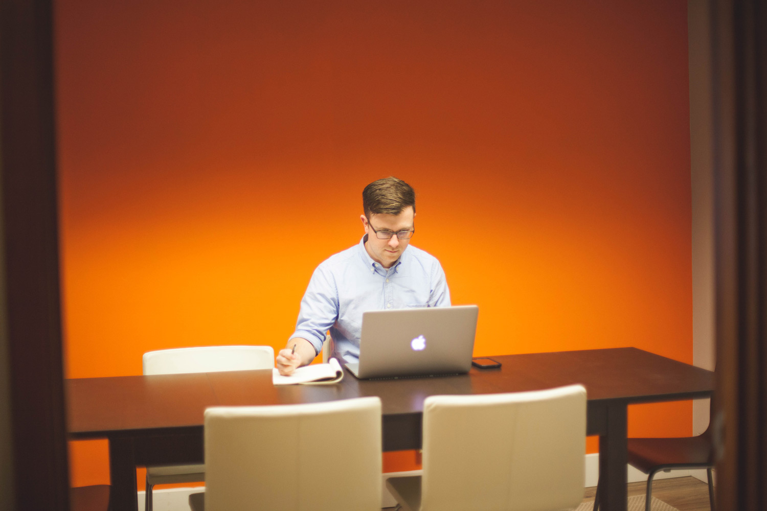 man in a blue shirt sitting at a large table working on a computer and writing in a notebook